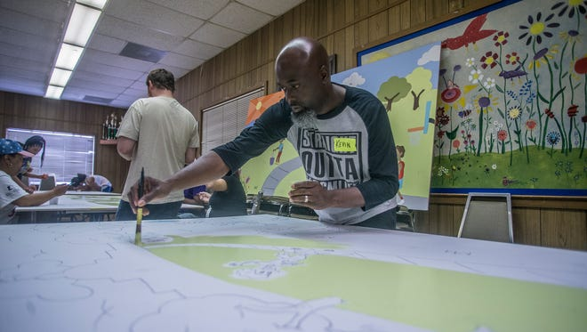 Kevin King, who drew all the images on the mural boards, paints by numbers with volunteers at the E.D. Nixon Community Center on Saturday, June 23, 2018.