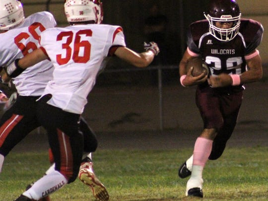 Tularosa's Caleb Ball, right, finds a hole to run through while being pursued by Eunice's Michael Copeland.