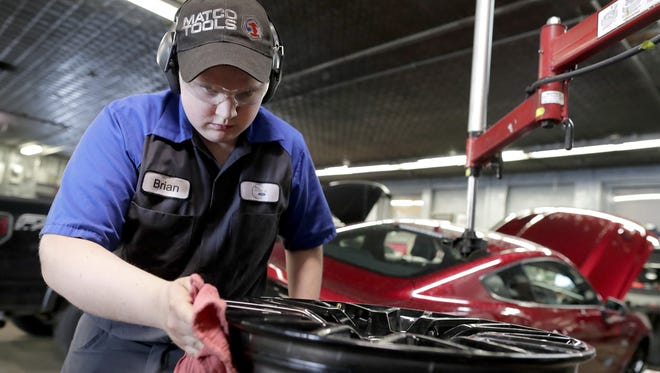 High School and technical college student Brian Dorschner works on a car last week at All World Ford in Hortonville.