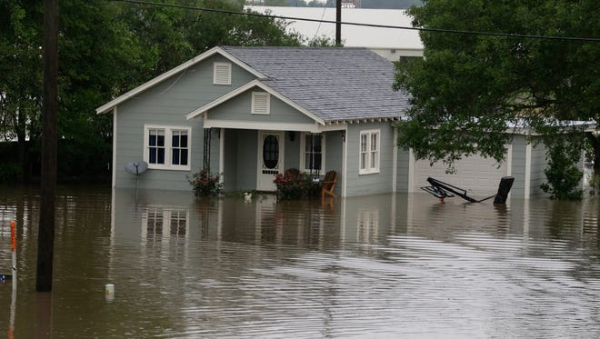 A home is surrounded by floodwaters near the Grand Coteau exit of  Interstate 49 as flash floods swept through Acadiana.