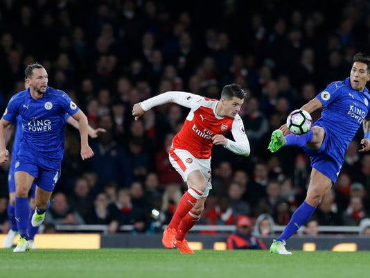 Leicester City's Leonardo Ulloa, right, clears the ball from Arsenal's Granit Xhaka during the English Premier League soccer match between Arsenal and Leicester City at the Emirates Stadium in London, Wednesday, April 26, 2017. (AP Photo/Alastair Grant)