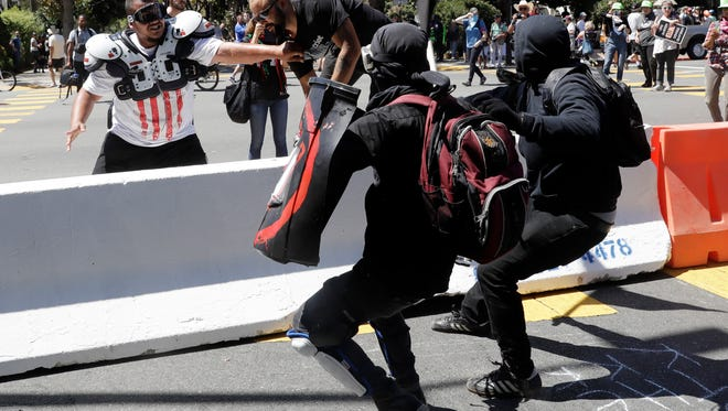 """Demonstrator Joey Gibson, second from left, is chased by anti-fascists during a free speech rally Sunday, Aug. 27, 2017, in Berkeley, Calif. Several thousand people converged in Berkeley Sunday for a """"Rally Against Hate"""" in response to a planned right-wing protest that raised concerns of violence and triggered a massive police presence. Several people were arrested for violating rules against covering their faces or carrying items banned by authorities. (AP Photo/Marcio Jose Sanchez)"""