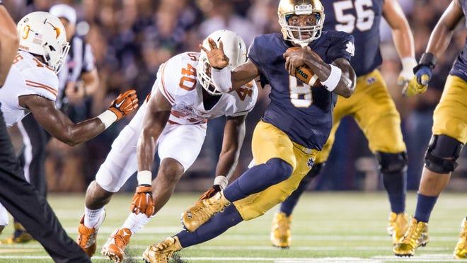 Sep 5, 2015; South Bend, IN, USA; Notre Dame Fighting Irish quarterback Malik Zaire (8) runs the ball as Texas Longhorns defensive end Naashon Hughes (40) pursues in the second quarter at Notre Dame Stadium. Mandatory Credit: Matt Cashore-USA TODAY Sports