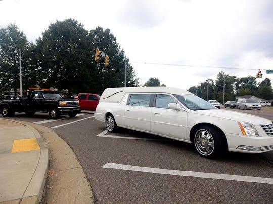 Wreckers follow a hearse carrying the body of Denton's Wrecker Service co-founder A.B. Denton on Wednesday.