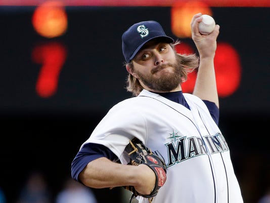 """FILE - In this May 10, 2016, file photo, Seattle Mariners starting pitcher Wade Miley throws against the Tampa Bay Rays during the first inning of a baseball game in Seattle. Miley hears the talk about lifting the bottom of the strike zone in an effort to spark offense and says there's been too much tinkering. """"I don't know why they just can't leave the game alone,"""" the Mariners pitcher said. (AP Photo/Elaine Thompson, File)"""
