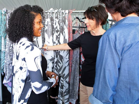 Project Runway season 12 designer Dom Streater (left) talks with two women during Wednesday's trunk show.