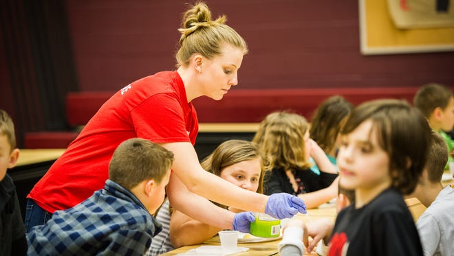 Maxine Herman, 20, serves pears as a snack for students in the YMCA's School Age Childcare Program at Dover Area Elementary School. Herman also plans to work this summer at a YMCA camp.