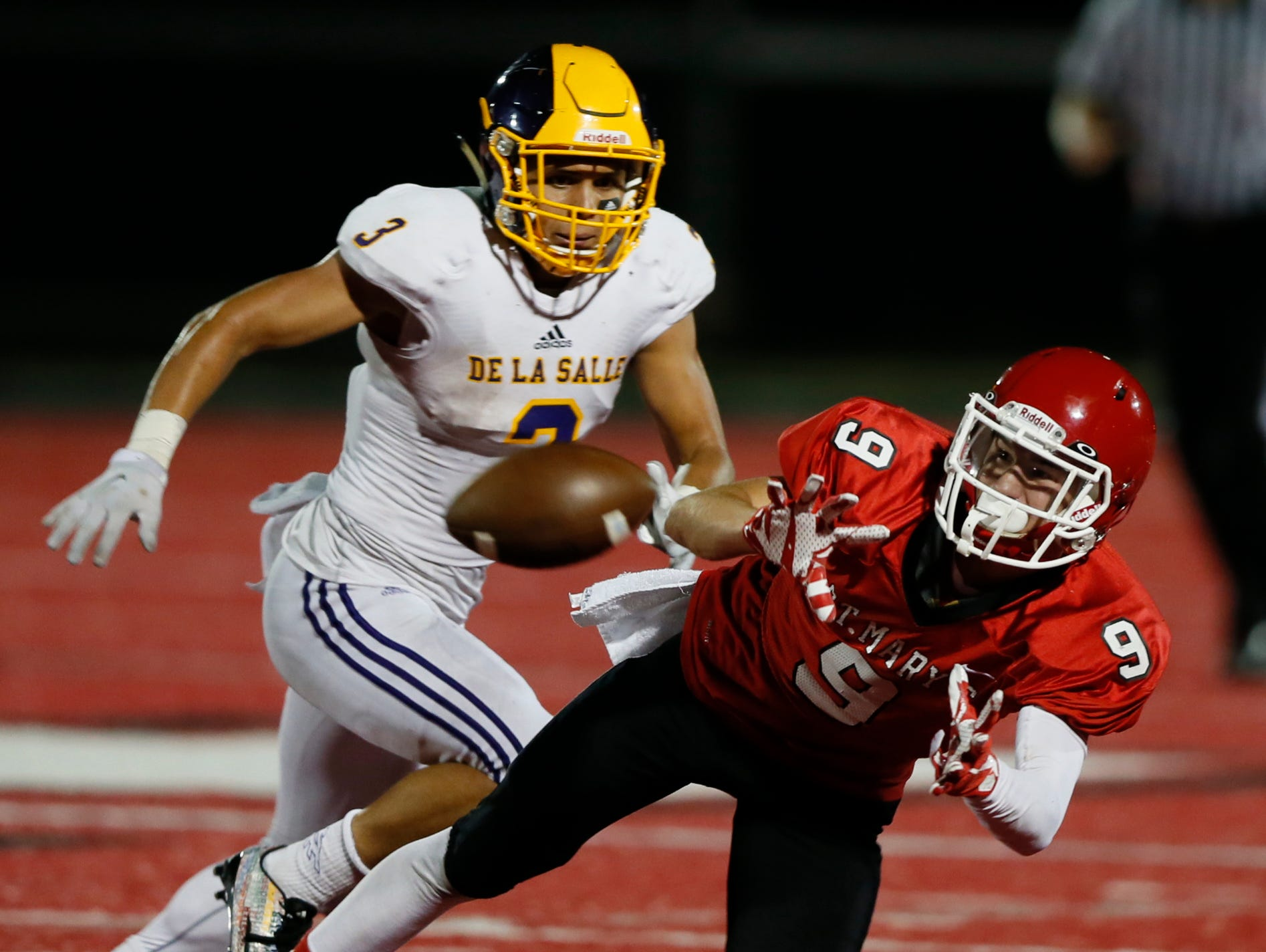 Orchard Lake St. Mary's Griffin Sheposh gets pass in his hands but bobbled it hitting the ground for an incomplete pass in front of Warren De La Salle Tru Wilson in the second half Friday at St. Mary's.
