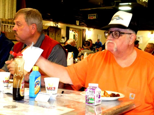 Rich Roth, right, grabs a napkin Wednesday during t the Kiwanis annual pancake festival. To his left are Vince Reiter and John Fausnaugh, all of Fremont.