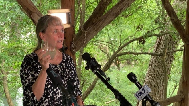 Teri Albright holds up a glass of opaque water taken from her home's well in Wimberley on Monday. A drilling mishap in March by a pipeline construction crew in Blanco County spilled tens of thousands of gallons of slurry into an underground aquifer, and Albright is now one of several people suing the drilling company.