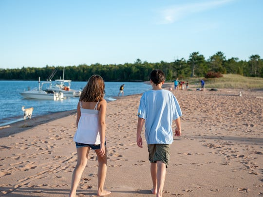 Meghan and Charlie Dougherty walk along the beach at