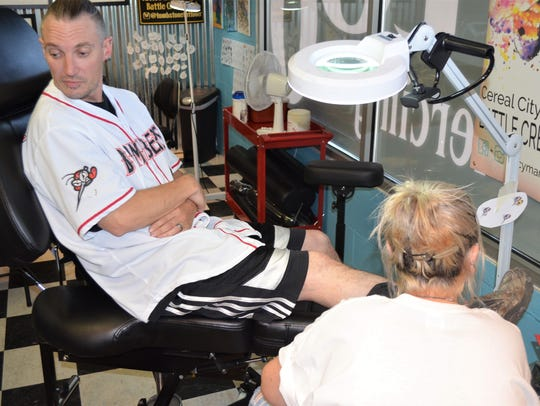 David Saxman gets his free Moe Skeeter tattoo at Cereal City Tattoo and Piercing, earning his free Battle Creek Bombers tickets for life.
