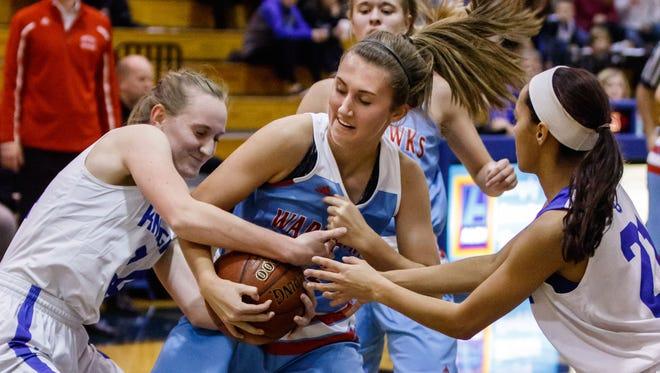 Arrowhead junior Lauren McDonald (center) battles for a rebound with Oak Creek's Lea Finn (left) and Kassandra Bartek (right) during the game at Oak Creek on Friday, Nov. 17.