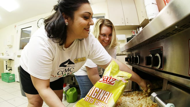 Volunteers Angie Torrez and Marie Van Zandt (back) prepare a tuna casserole for the residents of A New Leaf at Autumn House on Nov. 8, 2017, in Mesa, Ariz. Most people stay in the shelter for 30 to 45 days but can stay up to four months.