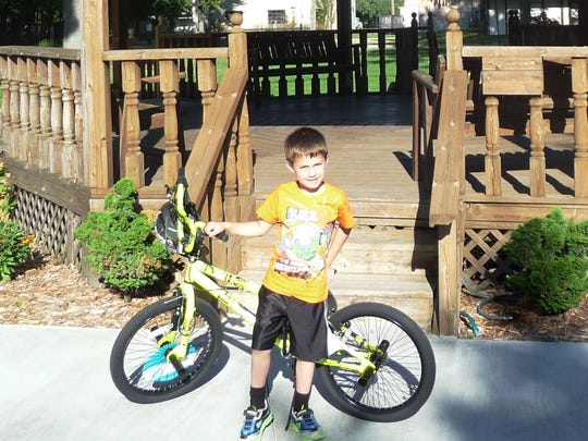 Ryan Schank, 6, of Melvin, won a 20-inch freestyle bicycle in the Sanilac County 4-H Fair/D.A.R.E. bicycle drawing Aug. 25. Drug Task Force members and D.A.R.E. instructors answered questions, accepted entries for the bicycle drawing and distributed wrist bands and pencils at the Sanilac County 4-H Fair.