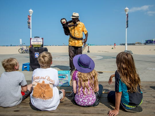 The Amazing Josini, Joseph Smith, banters with a monkey puppet as children gather to see him perform magic and comedy on the boardwalk in Ocean City.