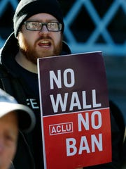 """Eric Buerk, of Seattle, holds a sign that reads """"No Wall No Ban,"""" during a protest, Wednesday, Dec. 6, 2017, outside a federal courthouse in Seattle."""