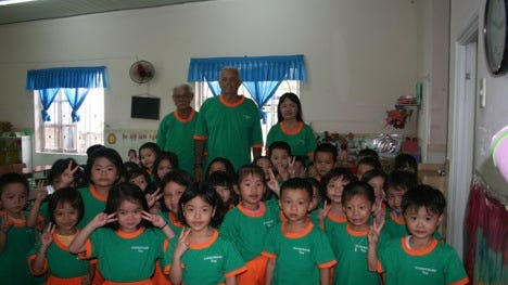 In the back from left to right are Sau Anh, vice chairman of the local Peoples Committee, Dave Baker, and Bich Lin, director of all daycares in Phuc Dong Province. In front are about 30 children who were among recipients of the more than 300 school uniforms that Baker donated.
