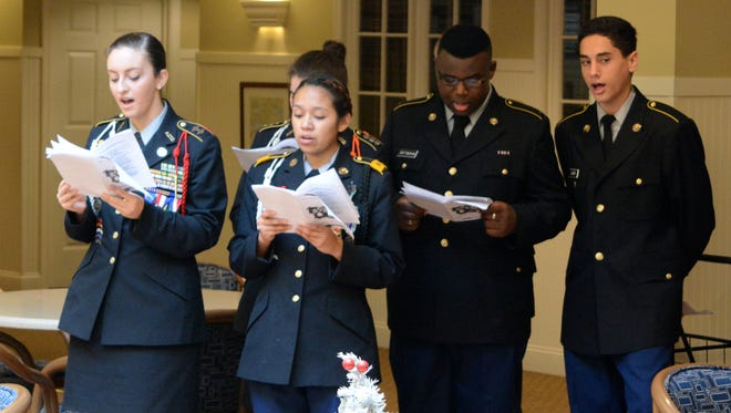 Cadets from Cape Henlopen High School's JROTC program sing Christmas carols to residents at the Cadbury at Lewes retirement community.