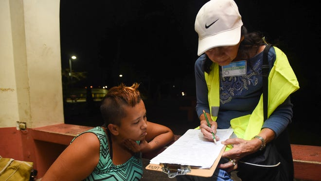 Lou Klitzke, right, conducts a survey with Jessilyn Ann Babauta, a 26-year-old homeless mother of four children, during the Guam Homeless Coalition's annual Point-In-Time Homeless Count at Paseo de Susana Park in Hagåtña on Jan. 26, 2018.