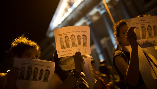 """Women, some holding photographs of the five men known as """"La Manada"""" or """"The Pack"""" and reading: """"Rapists"""" and """"We don't want your photos but your heads,"""" march outside the Spanish parliament during a protest in Madrid, Thursday, April 26, 2018."""