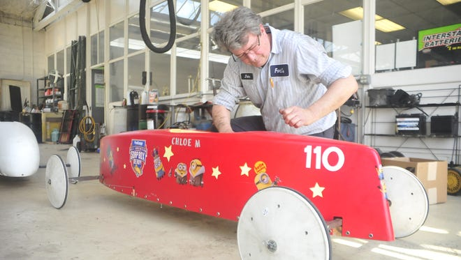 John Fort looks over a derby car that will race during this summer's North Central Ohio Soap Box Derby downtown Mansfield.