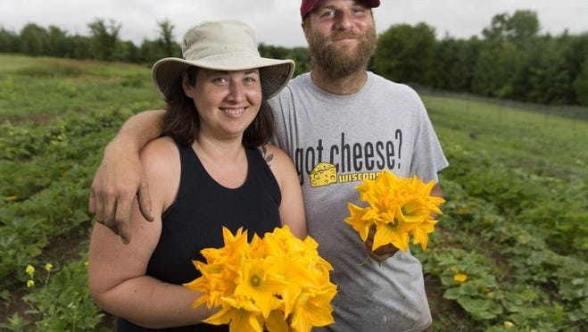 Jaime (left) and Drew Baker show off freshly picked squash blossoms at their small farm, called Love Rock Farm, near New Glarus. Jaime is one of 17 farmers, nationwide, recently accepted into a program that mentors people on a wide range of agricultural practices.