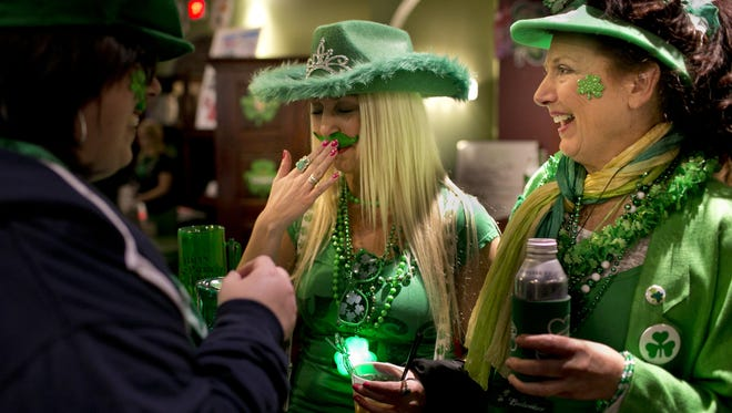 Jennifer Novak, of St. Clair, laughs and presses her green mustache back on while standing with Tina Mosher, of Marysville, left, and Kathy Novak, of St. Clair, during the Pub Crawl on last year at Lynch's Irish Tavern in downtown Port Huron.