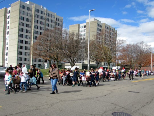 Participants march down South Main Street in Elmira
