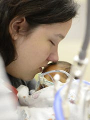 Brianna Galluzzo kisses her four-week-old son's forehead, Aug. 8, 2014, while holding him for only the second time at Arkansas Children's Hospital in Little Rock. The 18-year-old mother and husband, Anthony Galluzzo, 20, faced the traumatic decision whether to stop life support for Liam or let him live a machine-dependent life until he died.