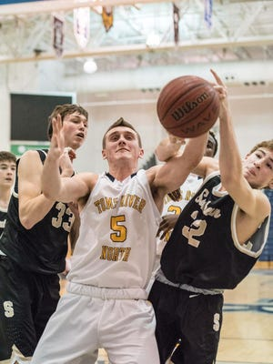 Hunter Petrick (5) of Toms River North is sandwiched between Southern's Peyton Wejnert (33) and Jake Dubois (32) while going for a loose ball on Jan. 29, 2016 in a Class A South game.
