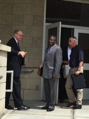 Chief Assistant District Attorney Michael Korchak, left, and defense lawyer Allen Stone, center, leave Broome County Court after closing arguments in Dwight Burton's murder trial.