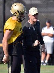 Purdue head coach Jeff Brohm (right) talks to quarterback David Blough