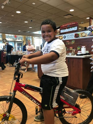 Issy Springs, 8, of St. Joseph, poses with the new bike gifted to him Aug. 31 by a Stearns County deputy in the Kwik Trip store where they met, on Stearns County roads 120 and 4.