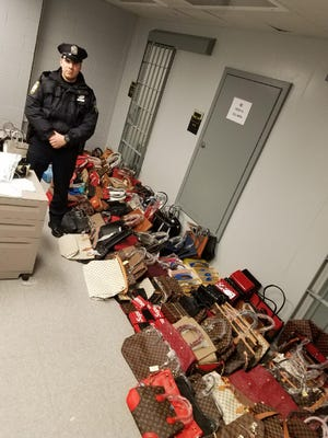 Port Authority Police Officer Christopher Roncancio with the counterfeit bags