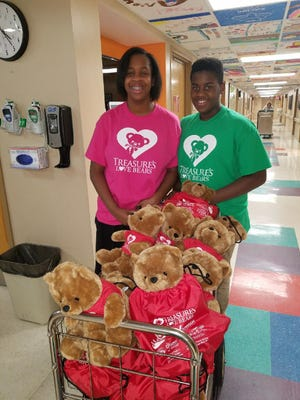 Treasure and Gregory Thaxton push a cart of bears through the hospital hallway on Wednesday.