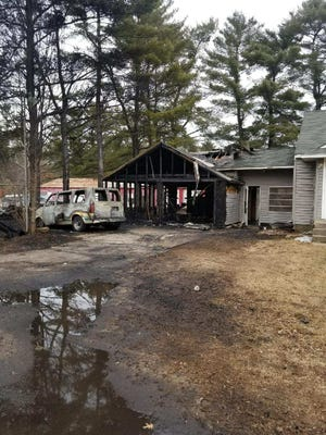 A structure fire in Grand Rapids damaged a porch, garage and two vehicles.