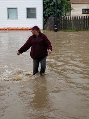 Jason Levine navigates flood water on Main Street in