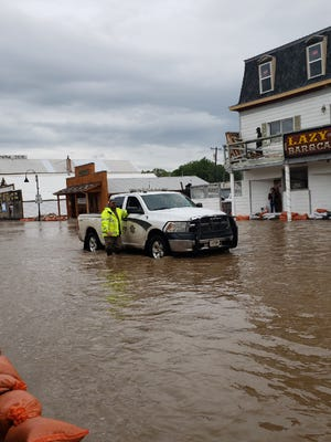 Jay Shalz, a state of Montana employee, and Lewis and Clark Sheriff Deputy Jerome Steiner assess the flood water on Main Street in Augusta Tuesday.
