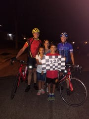 Stevens Point's Rob Hoffman (left) and Brad Nelson (right) are greeted by Hoffman's wife Bianca, and grandchildren Jayden Hoffman and Audrey Hoffman after completing their 220-mile bike ride from central Wisconsin to St. Paul on July 21.
