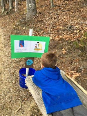 A child rests and reads the book featured along a StoryWalk.