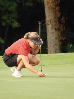 Pekin's Rachel Filarski places her golf ball on the green during the Dragons' early-season match against Macomb at Lick Creek Golf Course. Lick Creek will be the site of the Lady Dragon Classic girls golf tournament Saturday.