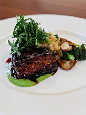 Braised short rib served with braised broccolini , fennel frond garnish.