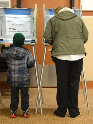 Candace Krist votes whike her son Joe checks out a voting booth at the Allouez Village Hall on Tuesday morning, Nov. 4, 2014.