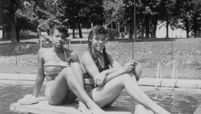 Two unidentified young women relax on the diving board at the Montgomery Hall Park pool in this undated photo.