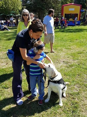 Julie Case, owner of Ultimate Canine, introduces 7-year-old TJ Durbin to his service dog, Sunny.