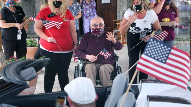 """World War II veteran Bernard """"Bernie"""" Ott holds a flag and waves during a parade in celebration of his 100th birthday Wednesday afternoon outside of The Inn at University Village in Massillon. Michelle Macksyn (left), resident care coordinator, and Amy Joy (right), executive director at the facility, are also pictured."""