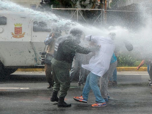 A demonstrator is pushed by a National Guard trooper