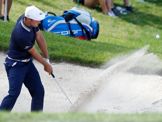 Bryson DeChambeau hits out of a bunker onto the 18th green during the third round of the John Deere Classic golf tournament, Saturday, July 15, 2017, at TPC Deere Run in Silvis, Ill. (AP Photo/Charlie Neibergall)
