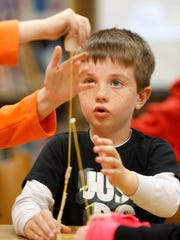 Nicholas Coleman, 7, keeps an eye on his team's structure as Alexis Gould, 8, tops off their spaghetti tower with a marshmallow during a Makers Fair on March 24 at Beaver Creek Elementary in Johnston.